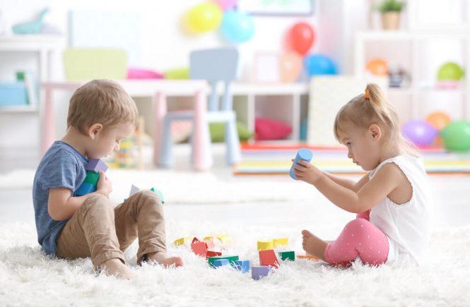 två barn som leker med klossar