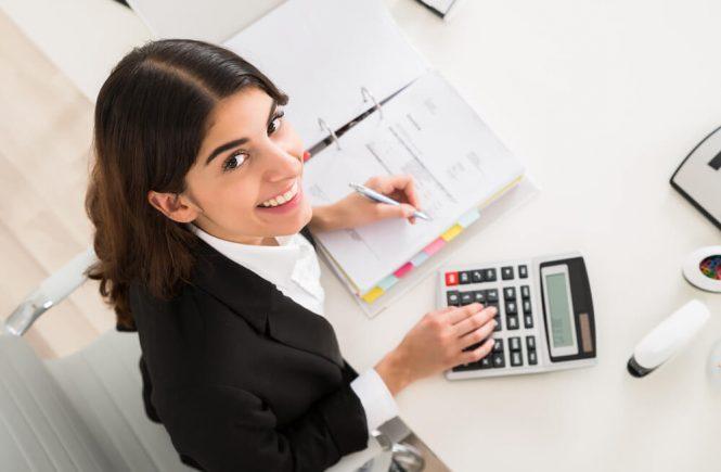 Kvinna på redovisningsbyrå med räknare